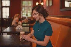 Eftertänksam nätt flicka i klassiskt sammanträde för elegant klänning på kafét som går att dricka kaffe arkivbilder