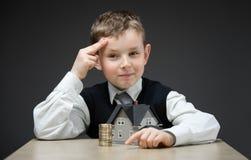 Eftertänksam pojke med den hem- modellen och hög av mynt Arkivbild