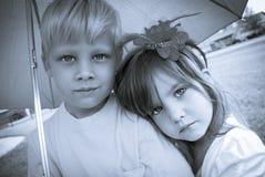 Pojke och flicka under paraplyet Fotografering för Bildbyråer