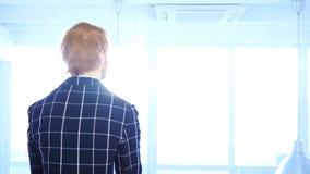 Eftertänksam rödhårig manaffärsman Looking till och med kontorsfönstret, baksidasikt Fotografering för Bildbyråer