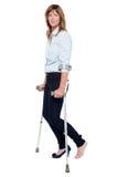 Eftertänksam seende kvinna som använder kryckor för att gå royaltyfri bild