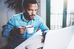 Eftertänksam skäggig afrikansk man som använder bärbar datorhemmet, medan dricka svart kaffe för kopp på trätabellen Begrepp av b royaltyfria bilder