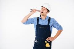 Eftertänksam stilig ung byggmästare som tänker och ser rymma upp skiftnyckeln fotografering för bildbyråer