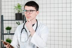 Eftertänksam stilig ung manlig doktor som använder minnestavladatoren Teknologier i medicinbegrepp fotografering för bildbyråer