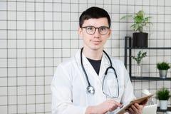Eftertänksam stilig ung manlig doktor som använder minnestavladatoren Teknologier i medicinbegrepp royaltyfri foto