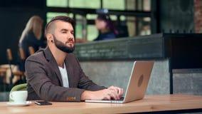 Eftertänksam tillfällig ung stilfull affärsman som skriver text på tangentbordet genom att använda bärbara datorn arkivfilmer