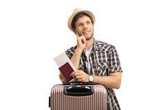 Eftertänksam turist med en resväska och ett pass Royaltyfri Fotografi