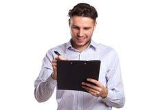 Eftertänksam ung affärsman Holding en minnestavla och en penna Royaltyfri Bild