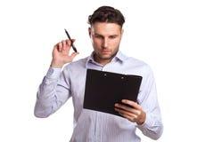 Eftertänksam ung affärsman Holding en minnestavla och en penna Royaltyfri Fotografi