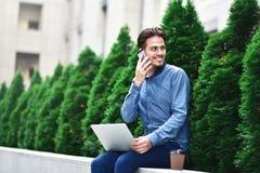 Eftertänksam ung caucasian man som använder bärbara datorn för att prata direktanslutet arkivfoton