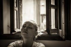 Eftertänksam ung kvinna med stängda ögon som är borttappade i tankar som kopplar av och drömmer nära öppnat fönster i svartvit fä Fotografering för Bildbyråer