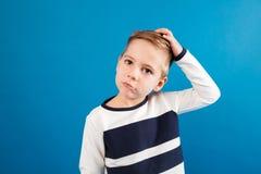 Eftertänksam ung pojke i tröjan som trycker på hans huvud royaltyfri foto