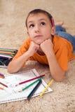 Eftertänksam unge med blyertspennor på mattan Royaltyfria Foton