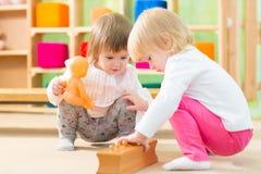 Eftertänksamma ungar som spelar i dagisrum royaltyfri foto