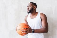 Eftertänksamt attraktivt idrottsmananseende vid väggen med bollen i hans armar Arkivbilder