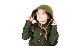 Eftertänksamt barn i militär likformig och hjälmen som bort ser royaltyfri fotografi
