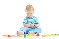 Eftertänksamt barn som leker logiska bildas toys Arkivbild