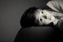 Eftertänksamt barn som ser in i kameran skuggor Black&White Arkivfoto