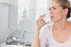 Eftertänksamt blont kvinnadricksvatten Royaltyfri Bild