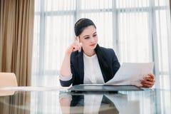 Eftertänksamt kontor för dokument för affärskvinna läst royaltyfri bild