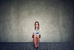 Eftertänksamt ledset affärskvinnasammanträde på en stol royaltyfri fotografi