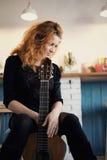 Eftertänksamt rödhårigt flickasammanträde med en gitarr arkivfoton
