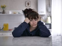Eftert?nksam kvinna som sitter med fj?rrkontroll p? en suddig bakgrund av k?ket royaltyfri foto
