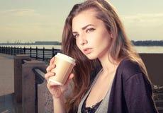 Eftertänksam ung moderiktig kvinna som tillbaka dricker plats för kaffe för tagande bort och för lutande granitstaket för anseend Arkivbilder
