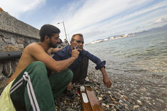 Кefugee shaves the other on the beach. Many refugees come from Royalty Free Stock Image