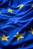EG sjunker Euroen sjunker Flagga av europeisk union som vinkar i vinden Detaljerat stjärnaflaggaeuro arkivbilder