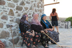 Egeïsch gebied - oude dorpsbewonervrouwen die bij de windmolen zitten Royalty-vrije Stock Foto
