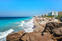 Egeïsch strand met sunshades in stad van Rhodes Rhodes, Griekenland stock fotografie