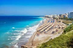 Egeïsch strand met sunshades in stad van Rhodes Rhodes, Griekenland stock afbeeldingen
