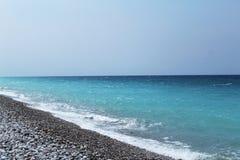 Egeïsch zeegezicht: turkooise blauwe overzees en rotsachtig strand stock fotografie
