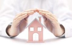 Egenskap insurance Husminiatyr som täckas av händer arkivbilder