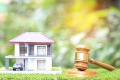 Egenskapsauktion, träauktionsklubba och modellhus på naturlig grön bakgrund, advokat av den hem- fastigheten och äganderättegensk royaltyfria bilder