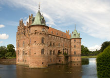 Egeskov castle in Denmark. Egeskov castle in Funen, Denmark with the moat and park against a blue sky with white clouds royalty free stock image
