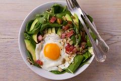 Egg с семенами квиноа, авокадоа, бекона, шпината и тыквы в белом шаре Стоковое Изображение RF
