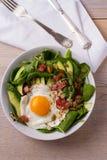 Egg с семенами квиноа, авокадоа, бекона, шпината и тыквы в белом шаре Стоковое Фото