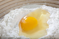 Egg. Raw egg lying on a flour in a wooden bowl Royalty Free Stock Images