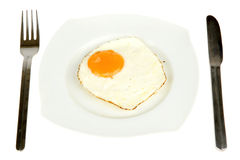 Egg. A plate with a fried egg, a fork and a knive Royalty Free Stock Photo