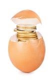 Egg agrietado se abren con las monedas de oro que salen contra Imagen de archivo libre de regalías