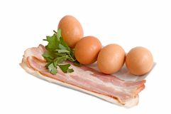 Egg and bacon. Egg, bacon and parsley on a plate Royalty Free Stock Images