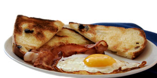An egg, bacon, raisin toast. A fried egg, crispy bacon and raisin toast on a white plate with a blue napkin isolated on white Stock Photography