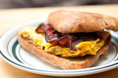 Egg and bacon sandwich. Scrambled eggs, cheese and crispy bacon sandwich on a toasted ciabatta bun Royalty Free Stock Image