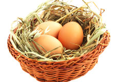 Egg in the basket. Three eggs in basket with the hay against the white background Royalty Free Stock Images