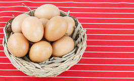 Egg in basket and red napery on desk Royalty Free Stock Photography