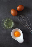 Egg beater and  eggs. Egg beater and  broken egg on dark background. Top view Stock Photos