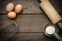 Egg beater. Rolling pin and eggs on wooden table Stock Photo