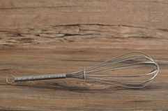 Egg beater. Whisk,  on a wooden background Royalty Free Stock Images